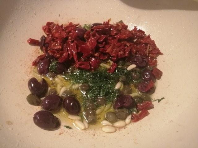 Cous cous allo zafferano con rana pescatrice pomodori secchi olive capperi pinoli e finocchietto selvatico
